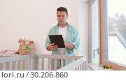 Купить «father with tablet pc and ruler measuring baby bed», видеоролик № 30206860, снято 18 февраля 2019 г. (c) Syda Productions / Фотобанк Лори