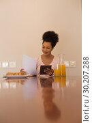 Купить «Woman looking at form while using digital tablet at home», фото № 30207288, снято 7 ноября 2018 г. (c) Wavebreak Media / Фотобанк Лори