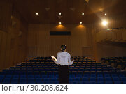 Купить «Businessawoman practicing and learning script while standing in the auditorium», фото № 30208624, снято 15 ноября 2018 г. (c) Wavebreak Media / Фотобанк Лори
