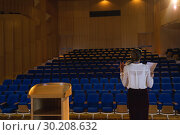 Купить «Businesswoman practicing and learning script while standing in the auditorium», фото № 30208632, снято 15 ноября 2018 г. (c) Wavebreak Media / Фотобанк Лори