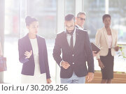 Business people interacting with each others in office lobby. Стоковое фото, агентство Wavebreak Media / Фотобанк Лори