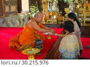 Буддистский монах повязывает веревочку-амулет   на руку женщине в буддистском храме. Бангкок, таиланд (2018 год). Редакционное фото, фотограф Виктор Карасев / Фотобанк Лори