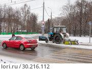 Купить «Уборка улиц в городе после снегопада. Трактор с навесной щеткой расчищает тротуар. По дороге едет ярко-красное авто», фото № 30216112, снято 21 февраля 2019 г. (c) Наталья Николаева / Фотобанк Лори