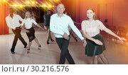 Купить «Active smiling people practicing lindy hop movements in dance class», фото № 30216576, снято 4 октября 2018 г. (c) Яков Филимонов / Фотобанк Лори