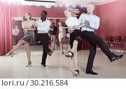 Купить «Young positive people practicing vigorous jive movements in dance class», фото № 30216584, снято 4 октября 2018 г. (c) Яков Филимонов / Фотобанк Лори