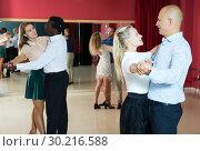 Купить «Positive people learning to dance classical dance together in dancing class», фото № 30216588, снято 4 октября 2018 г. (c) Яков Филимонов / Фотобанк Лори