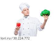 Купить «Difficult choice of pepper or broccoli - concept portrait of a chef with vegetables on a white background», фото № 30224772, снято 14 октября 2018 г. (c) Константин Лабунский / Фотобанк Лори