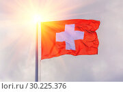 Купить «The national flag of Switzerland flutters in the wind against a blue cloudy sky.», фото № 30225376, снято 21 июня 2018 г. (c) Акиньшин Владимир / Фотобанк Лори