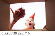Купить «happy birthday girl in party hat opening gift box», видеоролик № 30225716, снято 27 февраля 2019 г. (c) Syda Productions / Фотобанк Лори