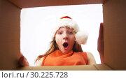 Купить «happy girl in santa hat opening christmas gift», видеоролик № 30225728, снято 27 февраля 2019 г. (c) Syda Productions / Фотобанк Лори
