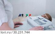 Купить «A medical clinic. A man receiving a ECG procedure. A results tape coming out of machine», видеоролик № 30231744, снято 14 июля 2020 г. (c) Константин Шишкин / Фотобанк Лори