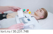 Купить «A man receiving a ECG procedure. A results tape coming out of machine», видеоролик № 30231748, снято 14 июля 2020 г. (c) Константин Шишкин / Фотобанк Лори