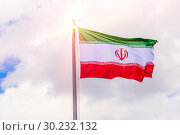Купить «The national flag of Iran flutters in the wind against the blue cloudy sky.», фото № 30232132, снято 21 июня 2018 г. (c) Акиньшин Владимир / Фотобанк Лори