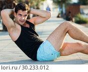 Купить «Man doing abs crunches outdoor», фото № 30233012, снято 14 августа 2017 г. (c) Яков Филимонов / Фотобанк Лори
