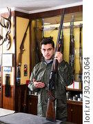 Купить «Man choosing rifle in shop», фото № 30233064, снято 11 декабря 2017 г. (c) Яков Филимонов / Фотобанк Лори