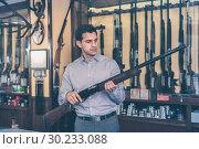 Купить «Handsome adult male in hunting shop with rifle in hands», фото № 30233088, снято 11 декабря 2017 г. (c) Яков Филимонов / Фотобанк Лори