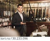 Купить «Handsome adult male in hunting shop with rifle in hands», фото № 30233096, снято 11 декабря 2017 г. (c) Яков Филимонов / Фотобанк Лори