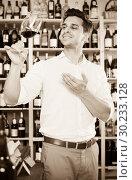 Cheerful man holding glass of red wine in winery section. Стоковое фото, фотограф Яков Филимонов / Фотобанк Лори