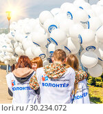 Купить «Russia, Samara, April 2016: young volunteers are preparing inflatable balls for the holiday of cosmonautics on a spring sunny day. Text in Russian: Samara youth house, volunteer, let's go.», фото № 30234072, снято 12 апреля 2016 г. (c) Акиньшин Владимир / Фотобанк Лори