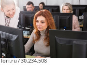 Купить «Young female teacher explaining computer skills to mature woman», фото № 30234508, снято 20 февраля 2019 г. (c) Яков Филимонов / Фотобанк Лори