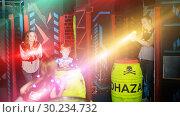 Купить «Kids and parents in beams during laser tag game», фото № 30234732, снято 6 июня 2018 г. (c) Яков Филимонов / Фотобанк Лори