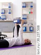 Купить «Female employee doing sport exercises in the office», фото № 30237508, снято 6 ноября 2018 г. (c) Elnur / Фотобанк Лори