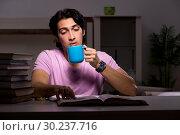 Купить «Male handsome student preparing for exams late at home», фото № 30237716, снято 15 ноября 2018 г. (c) Elnur / Фотобанк Лори