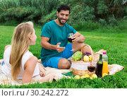 Купить «Smiling couple is sitting with wineglasses and talking», фото № 30242272, снято 10 августа 2017 г. (c) Яков Филимонов / Фотобанк Лори