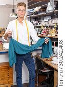 Купить «Fashion designer demonstrating dress», фото № 30242408, снято 20 октября 2018 г. (c) Яков Филимонов / Фотобанк Лори