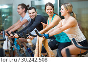 Купить «Group positive working out of cycling in fitness club», фото № 30242508, снято 18 сентября 2019 г. (c) Яков Филимонов / Фотобанк Лори