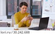 Купить «smiling businesswoman using smartphone at office», видеоролик № 30242688, снято 28 февраля 2019 г. (c) Syda Productions / Фотобанк Лори