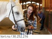 Купить «Woman farmer standing with white horse, man cleaning floor», фото № 30252216, снято 4 июля 2018 г. (c) Яков Филимонов / Фотобанк Лори