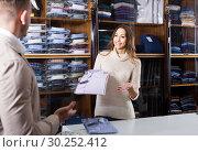Купить «Female shopping assistant offering various shirts in men's cloths store», фото № 30252412, снято 26 марта 2019 г. (c) Яков Филимонов / Фотобанк Лори