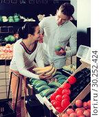 Купить «Couple choosing fruits in shop», фото № 30252424, снято 23 ноября 2016 г. (c) Яков Филимонов / Фотобанк Лори