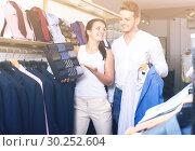Купить «Happy couple chousing jacket, shirt and tie», фото № 30252604, снято 24 октября 2016 г. (c) Яков Филимонов / Фотобанк Лори