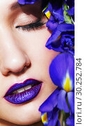 Купить «Portrait of young beauty female face with violet lips makeup and irist flowers near face», фото № 30252784, снято 4 марта 2019 г. (c) Serg Zastavkin / Фотобанк Лори