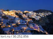 Купить «View of the city of Oia in the evening. Santorini Island in Greece», фото № 30252856, снято 10 июня 2017 г. (c) Наталья Волкова / Фотобанк Лори