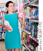 Купить «Charming female want to buying cleaners in bottle», фото № 30261172, снято 6 июня 2017 г. (c) Яков Филимонов / Фотобанк Лори
