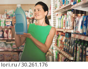 Купить «Beautiful female want to buying softener in bottle», фото № 30261176, снято 6 июня 2017 г. (c) Яков Филимонов / Фотобанк Лори