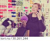 Купить «Woman with shopping bags using phone», фото № 30261244, снято 10 мая 2017 г. (c) Яков Филимонов / Фотобанк Лори