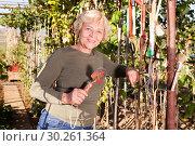 Купить «Woman holding garden tools», фото № 30261364, снято 3 октября 2018 г. (c) Яков Филимонов / Фотобанк Лори