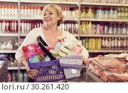 Купить «Glad female holding basket in shop», фото № 30261420, снято 20 декабря 2017 г. (c) Яков Филимонов / Фотобанк Лори