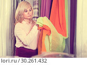 Купить «Mature woman seller showing curtain in the curtains shop», фото № 30261432, снято 17 января 2018 г. (c) Яков Филимонов / Фотобанк Лори