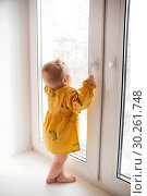 little girl of 9 months standing on window sill . Стоковое фото, фотограф Дарья Филимонова / Фотобанк Лори