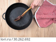 Купить «Empty black round pan with wooden handle and wooden spoon on a table, top view.», фото № 30262692, снято 11 февраля 2019 г. (c) age Fotostock / Фотобанк Лори