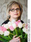 Купить «Красивая женщина среднего возраста с большим букетом тюльпанов», эксклюзивное фото № 30267488, снято 18 февраля 2019 г. (c) Игорь Низов / Фотобанк Лори