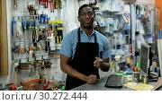 Купить «Portrait of confident owner of household goods store standing behind counter», видеоролик № 30272444, снято 11 февраля 2019 г. (c) Яков Филимонов / Фотобанк Лори