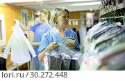 Купить «Two female dry-cleaning salon employees in process of work», видеоролик № 30272448, снято 11 февраля 2019 г. (c) Яков Филимонов / Фотобанк Лори