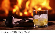 Купить «A man's hand pours whisky from a bottle into a glass on the background of a burning fireplace. Next to a glass of whiskey on the table are an open book and a smoking pipe», видеоролик № 30273248, снято 10 марта 2019 г. (c) Алексей Кузнецов / Фотобанк Лори