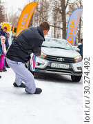 Купить «A man participates in the competition for the holiday Maslenitsa and drags a lightweight LADA car on a rope. City of Cheboksary, Russia, 03/10/2019.», фото № 30274492, снято 10 марта 2019 г. (c) Александр Якимов / Фотобанк Лори